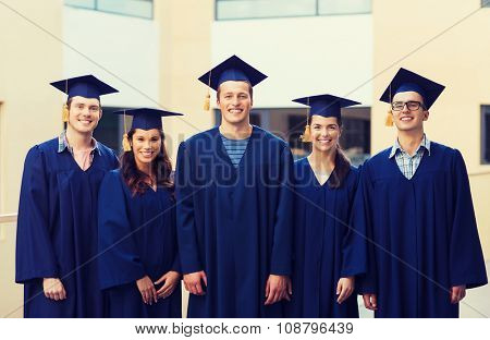 education, graduation and people concept - group of smiling students in mortarboards and gowns outdoors