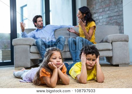 Children laying on the carpet in living room while parents arguing on the sofa
