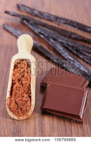 Powdery Cocoa, Dark Chocolate, Fragrant Vanilla Sticks On Wooden Surface