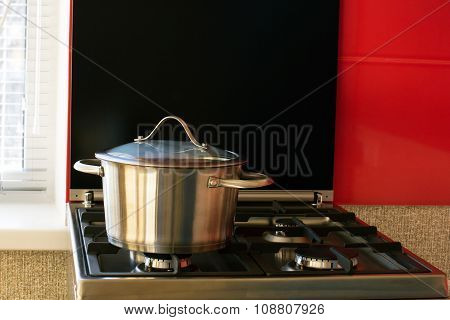 stainless saucepan on a gas stove in the kitchen poster