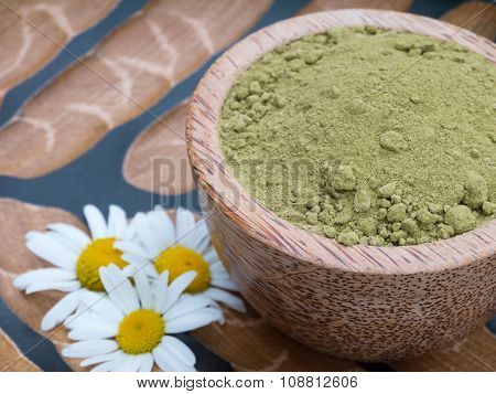 Henna Powder Hair Colourant In The Coconut Bowl And Chamomile Flowers