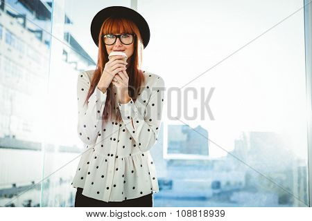 Smiling hipster woman drinking coffee in a bright room