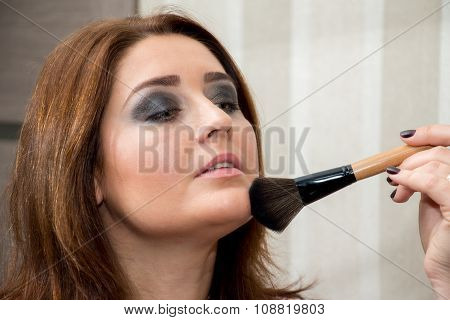 Beautiful Middle-aged Woman Powdering Her Face.