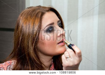 Middle-aged Woman Applies Lipstick On Her Lips.