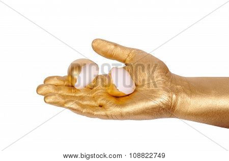 Golden hand holding eggshell on a white background