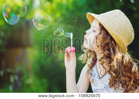 Little Girl Blowing Soap Bubbles In A Heart Shape. Happy Childhood Concept.