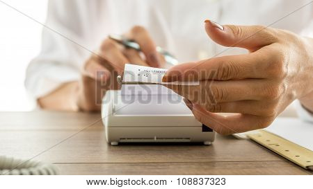 Woman Holding A Printout Receipt As It Comes Out Of Adding Machine