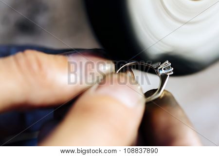 Handsome young jeweler polishing jewelry with tools poster