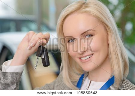 Smiling salesperson presenting a car key.