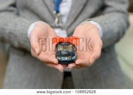 Small souvenir car in saleswomans hands.