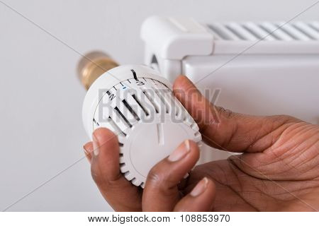 Person's Hand Holding Radiator Thermostat