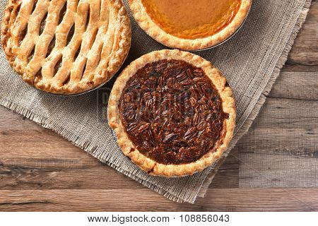 Three fresh baked Thanksgiving Pies. A Pecan Pie, Apple pie and Pumpkin pie seen from a high angle on a burlap and wood surface.
