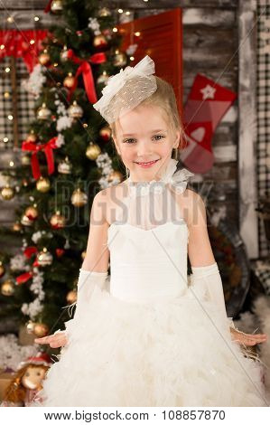 Cute Young beautiful girl in white Christmas dress is sitting on