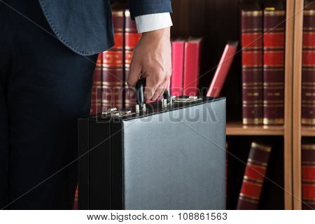 Lawyer Carrying Briefcase Against Bookshelf