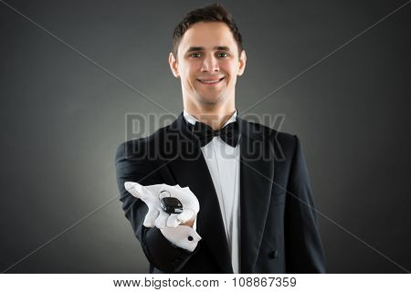 Portrait of happy young waiter giving car keys against gray background poster