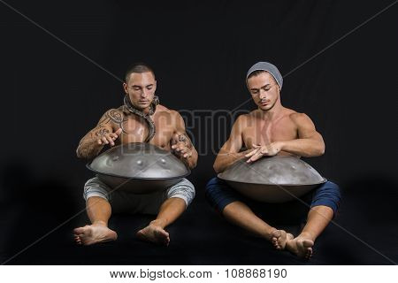 Male Drummers Drumming on Steel Drums in Studio