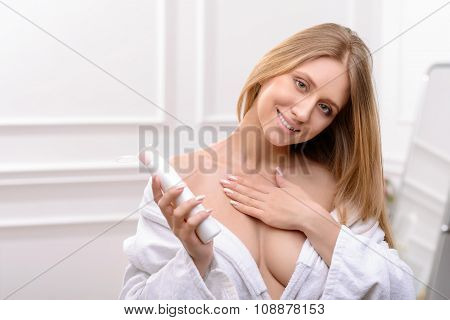 Pleasant woman using cream for body