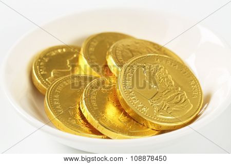 detail of chocolate coins in white bowl