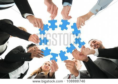 Directly below shot of business team joining jigsaw pieces in huddle against white background poster