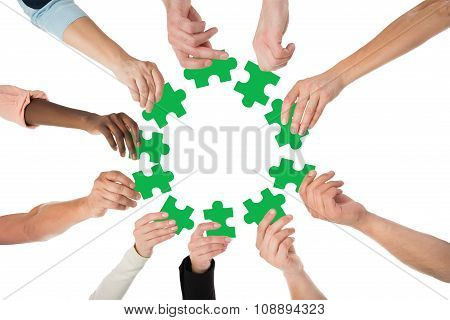 Creative Business People Holding Green Jigsaw Pieces