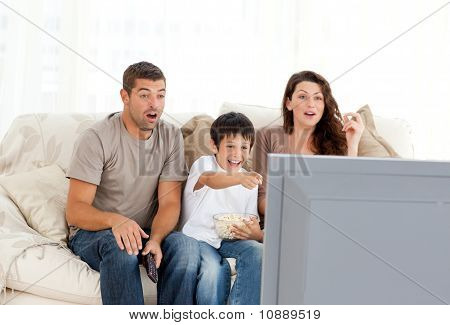 Happy Family Watching A Movie On Television Together On The Sofa