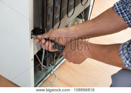 Serviceman Working On Fridge At Home