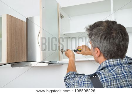 Serviceman Fixing Cabinet With Screwdriver In Kitchen