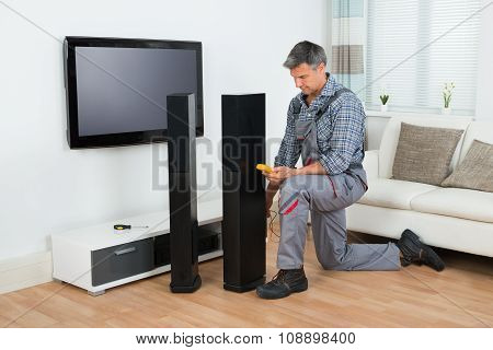 Technician Checking Tv Speaker With Multimeter