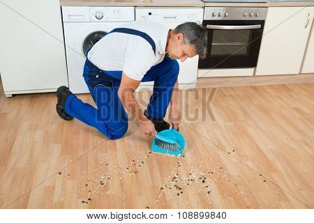 Janitor Sweeping Floor With Brush And Dustpan In Kitchen