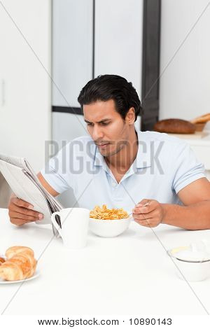 Serious Man Reading The Newspaper While Eating Cereals