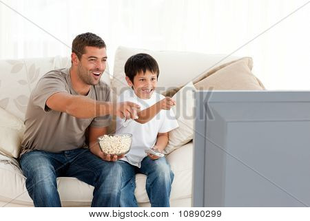 Happy Father And Son Watching Television While Eating Pop Corn