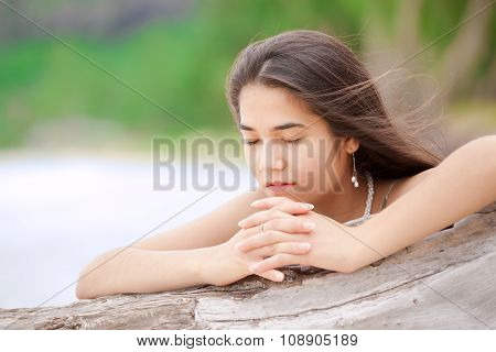 Beautiful Teen Girl On Beach Praying By Driftwood Log