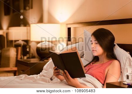 Biracial Teen Girl Reading Book  In Bed At Night