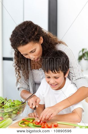 Attentive Mother Helping Her Son To Cut Vegetables