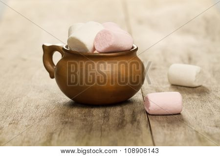 Sweet Marshmallows In A Clay Pot On Wooden Background