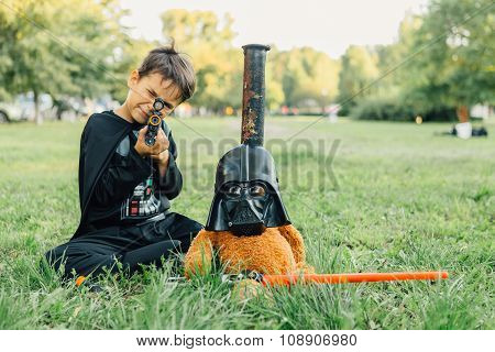 Boy In A Costume Of  Darth Vader And Teddy Bear In A Mask Of Darth Vader With Sword.