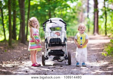 Children Pushing Stroller With Newborn Baby