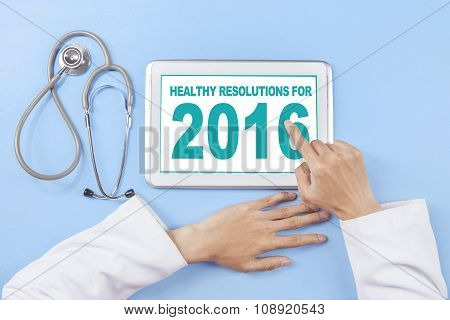 Doctor Writes Healthy Resolution For 2016 On Tablet