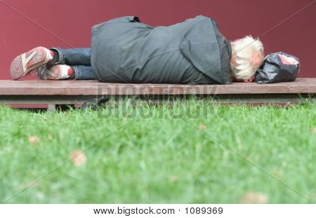 homeless elderly man lying on the bench. poster