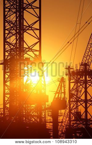 Industrial Background: Conceptual Photo Of Construction Facilities Against Bright Rising Sun