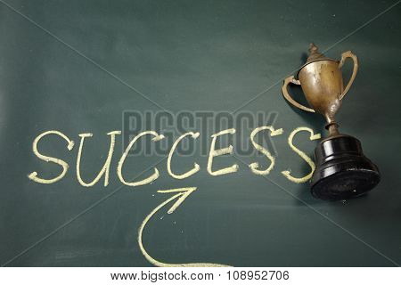 hand writting success and trophy on the blackboard