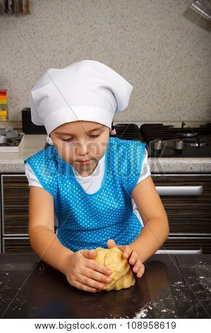 Little girl is kneading a dough in a kitchen poster