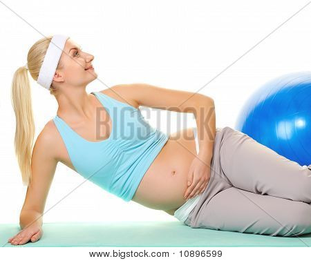 Young pregnant woman making exercise with a fitness ball