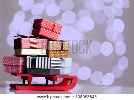 Wooden red sled full of gift boxes on grey background