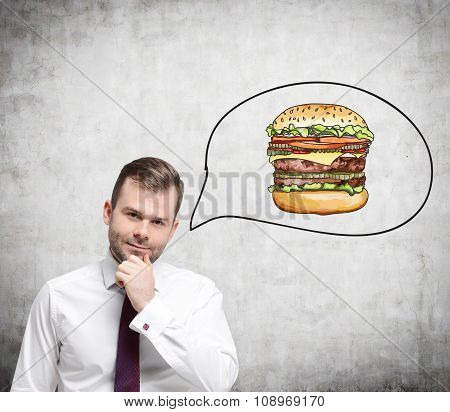 A Handsome Man Is Thinking About Burger. A Fast Food Concept. Concrete Background.