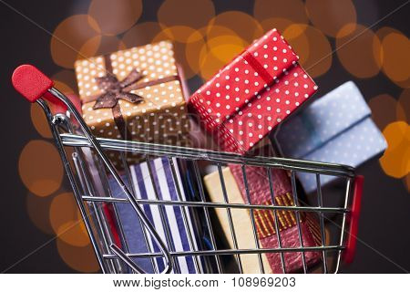 Shooping cart full of gift boxes on dark background