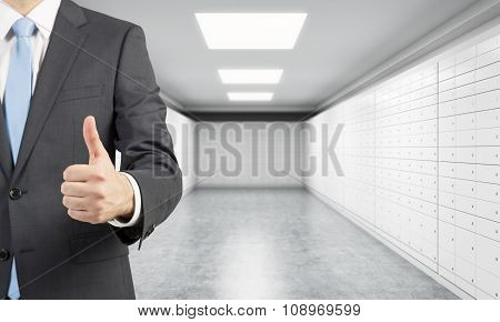 A Private Manger Of A Bank With Thumb Up Stands In A Room With Safe Deposit Boxes. A Concept Of Stor