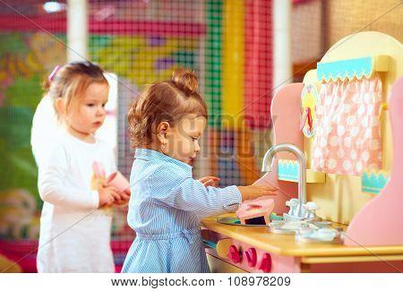 Little Girls Playing At Toy Kitchen In Kindergarten