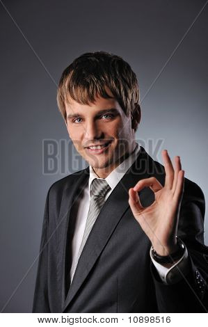 Cheerful businessman showing OK sign over grey background