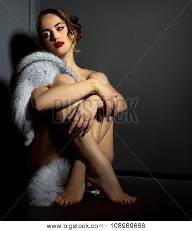 Sexual naked woman posing in chic fur coat